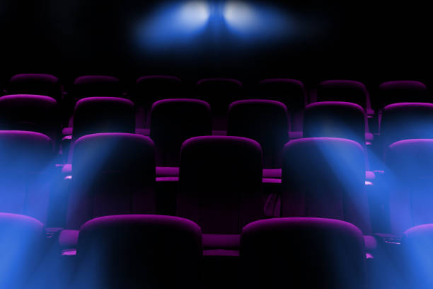 empty movie theater with purple seats with flare light rays from projector stock photo