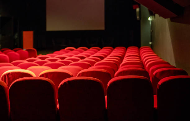 Empty movie theatre with red seats stock photo