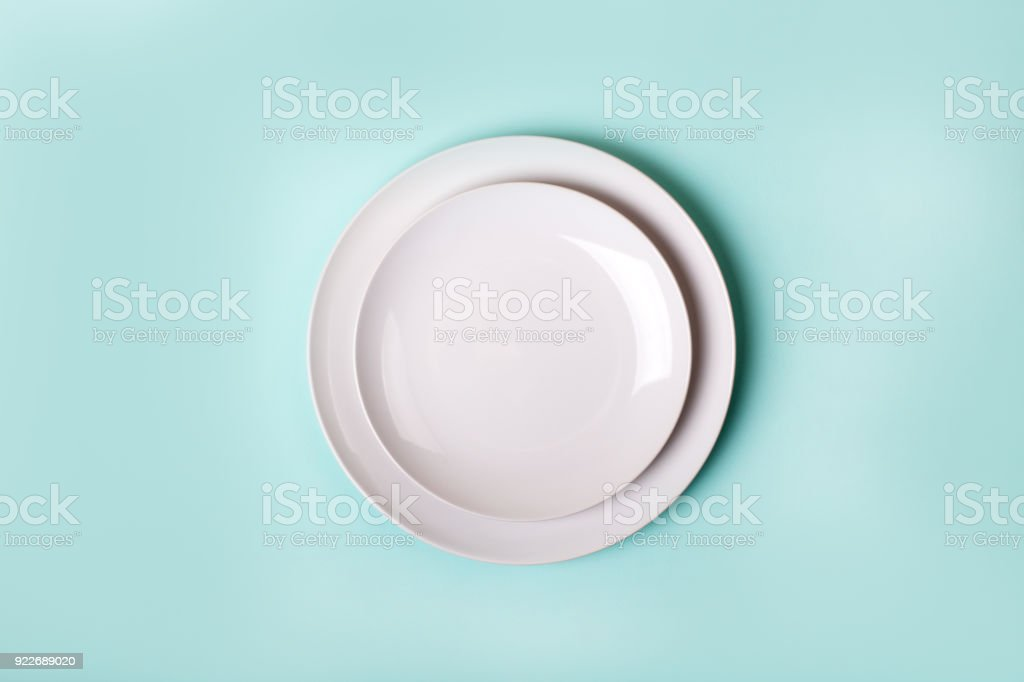 empty new ceramics plate isolated on turquoise background - top view