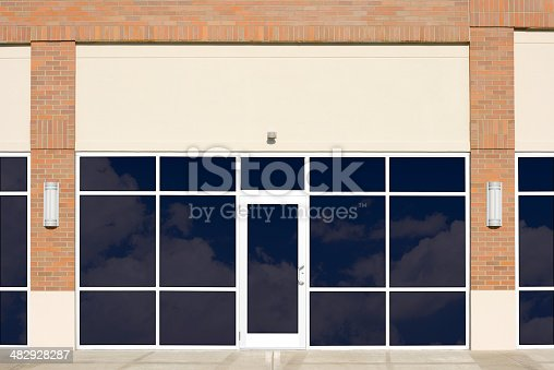 A brand new, blank generic store front, in a contemporary strip mall, with clouds reflecting in the windows. Note: a clipping path is included for the windows, making it easy for you to add whatever you would like to be in the windows.
