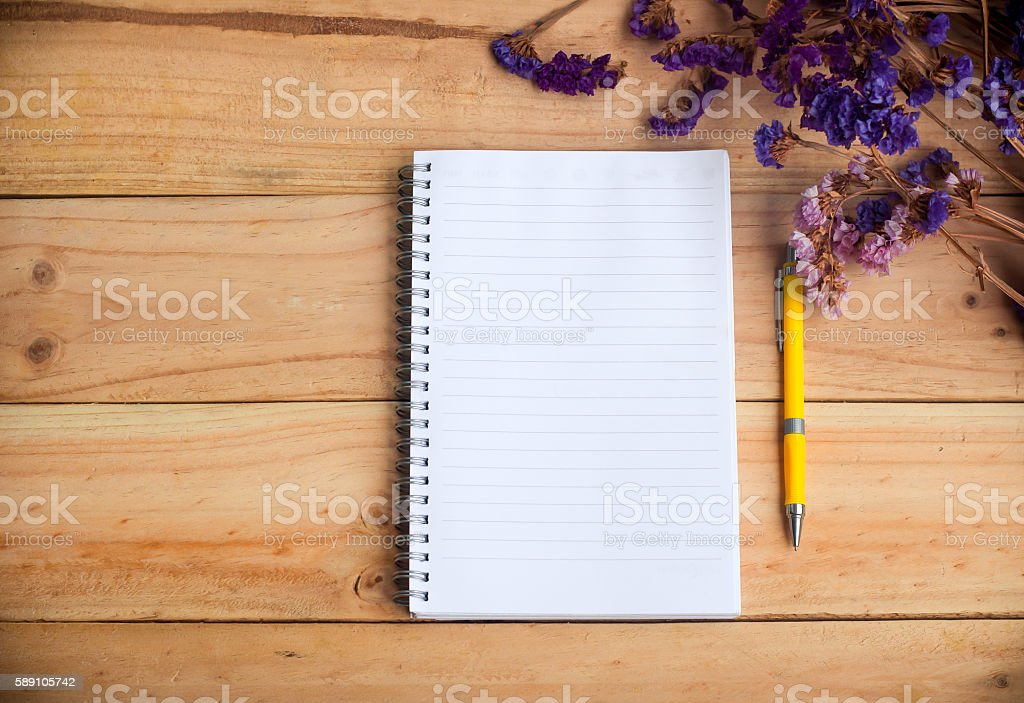 empty notebook and yellow pen with dried flower stock photo