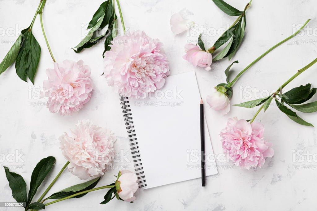 Leere Notebook für Planung, Bleistift und rosa Pfingstrose Blumen auf weißem Steintisch. Frau Arbeitstisch. – Foto