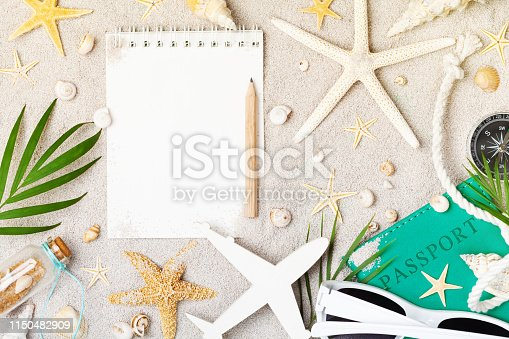 941183588 istock photo Empty notebook with accessories for planning summer holidays, travel and vacation on sand background top view. Flat lay. 1150482909