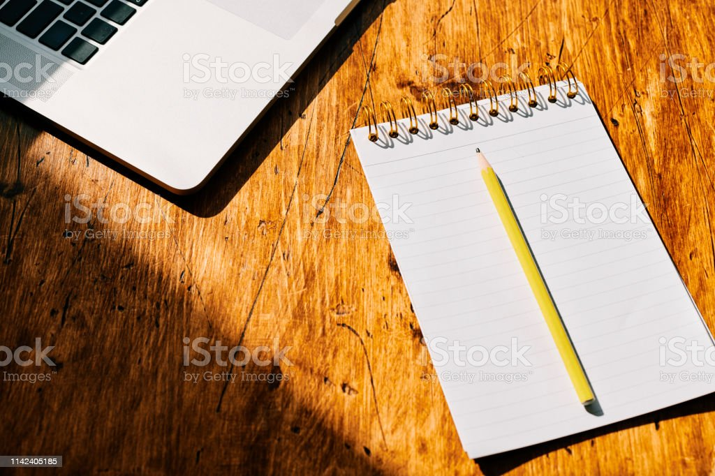 Empty notepad and laptop on a desk ink bright sunshine. stock photo