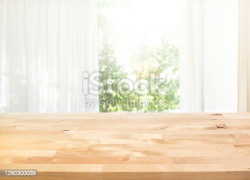 885452818 istock photo Empty of wood table top on blur of curtain with window view green from garden background 1260300039