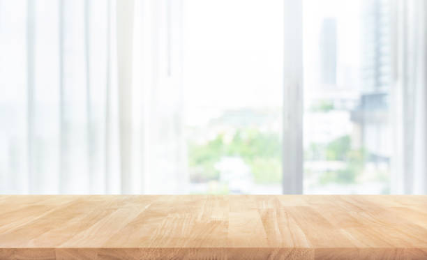 Empty of wood table top on blur of white curtain with window view background stock photo