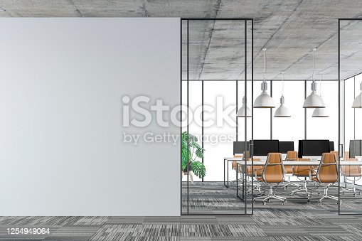 Empty office interior with copy space on carpet floor. Wordesks, lighting and computer equipment and windows in background behind glass door. Slight cross process effect added. 3D rendered image.