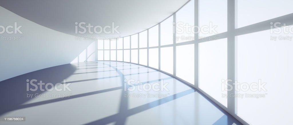 Leerer ovaler Büroraum mit Fensterfront im Sonnenlicht