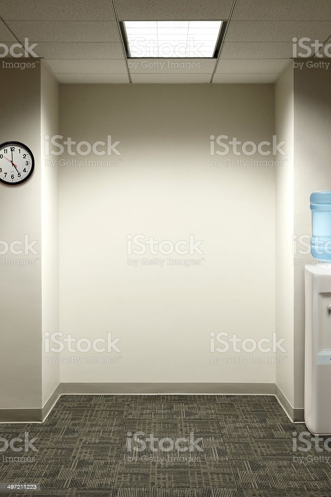 Empty office nook with watercooler and wall clock stock photo
