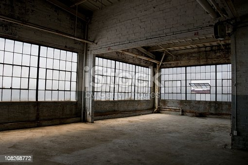 An abandoned dirty old factory room lit with natural light through industrial windows.