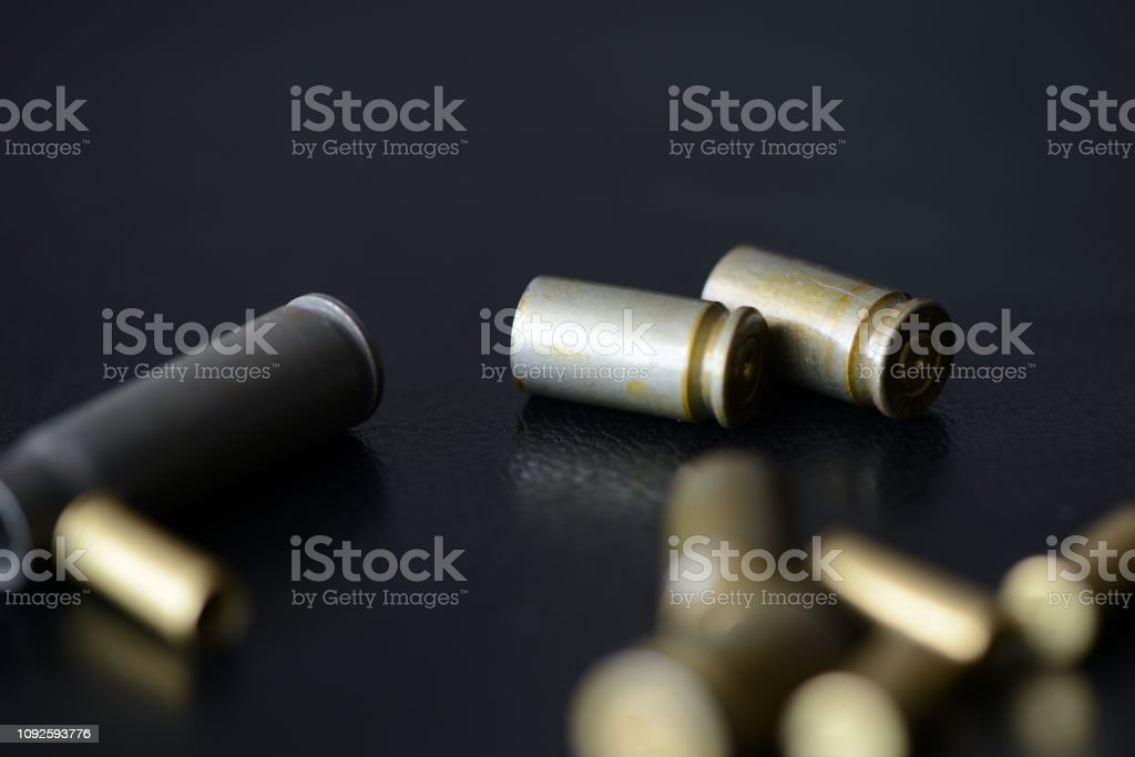 Empty old bullet cartridges on a dark background close up stock photo