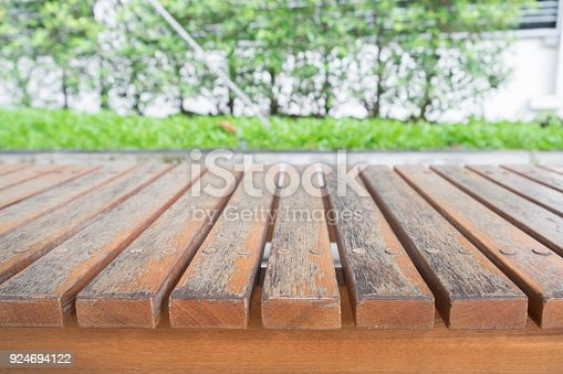 989111446istockphoto Empty old green wood table with backdrop blur nature soccer field background, for display your product and copy space. 924694122