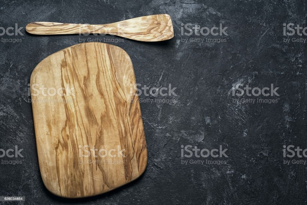 empty olive wood cutting board and wooden paddle for stirring stock photo
