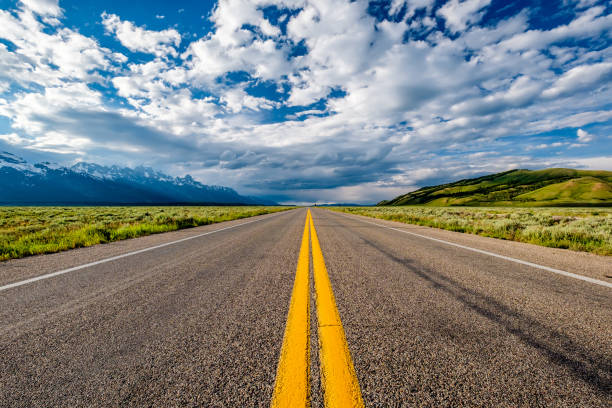 Empty open highway in Wyoming Empty open highway in Wyoming, USA straight stock pictures, royalty-free photos & images