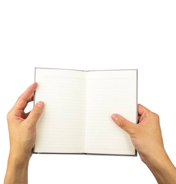 Empty opened notebook on hands holding isolated on white background, with clipping path stock photo