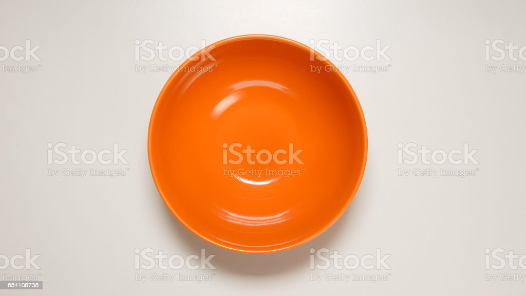 TOP VIEW: Empty orange dish on white table stock photo