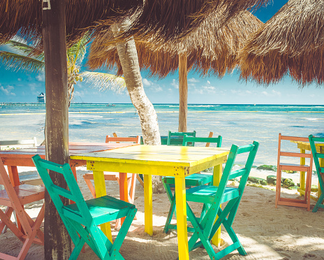 Colorful outdoor tables at the beach are empty