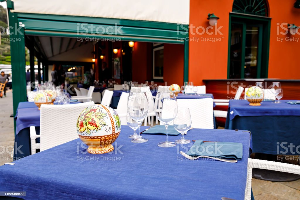 Empty outdoor restaurant table in Liguria, Italy. Laid table for...