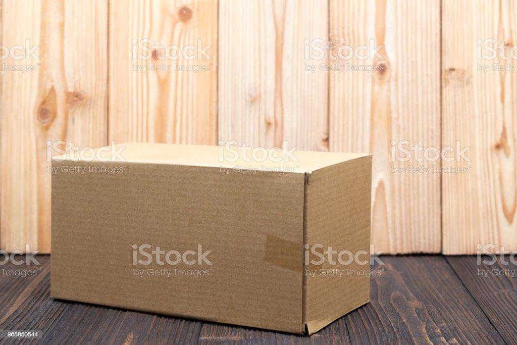 Leeg pakket bruine kartonnen doos of lade op houten achtergrond, mock up. - Royalty-free Achtergrond - Thema Stockfoto