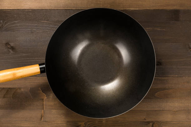 Empty pan isolated on wooden background stock photo