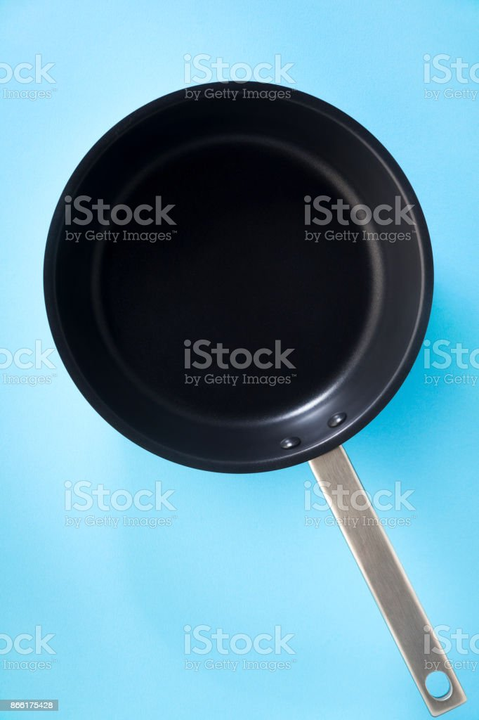 empty pan with non-stick coating and a steel pen isolated on blue stock photo