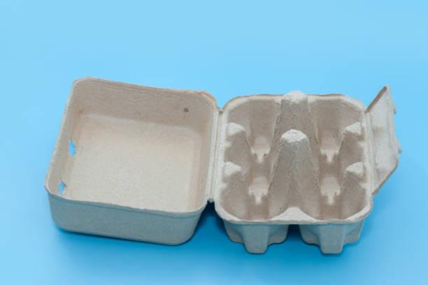 leeres papier tablett eierkarton auf blauem hintergrund - eierverpackung stock-fotos und bilder