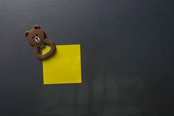 Leeres Papier auf Kühlschranktür mit Bär Gesicht Magnet. – Foto