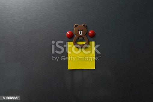 istock Empty paper on refrigerator door with bear face magnet. 826668652