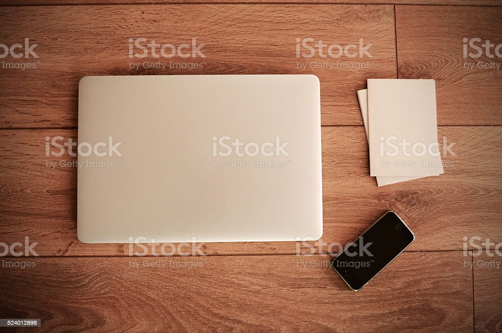 Empty paper, phone and laptop on wooden table top view stock photo