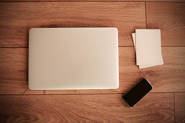 empty paper, phone and laptop on wooden table top view - closed stock photos and pictures