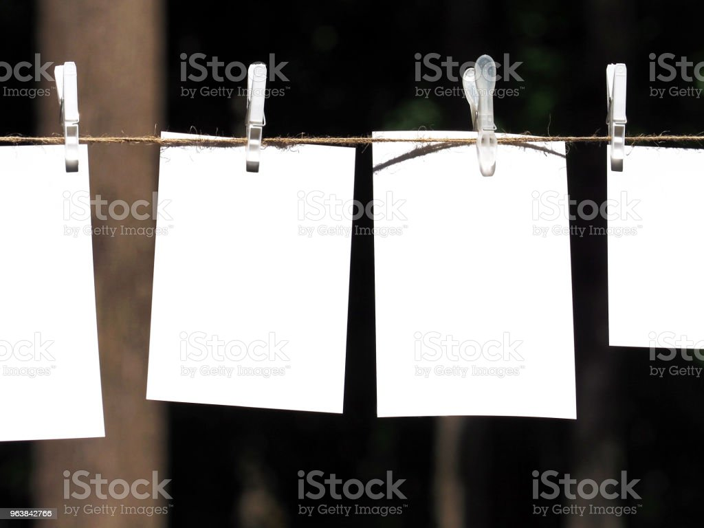 Empty paper sheet frames hanged by colored clothespins on dark nature  background. Blank cards on rope. Mock up for display of design, memo or congratulations backdrop. Pieces of paper, posters - Royalty-free Abstract Stock Photo