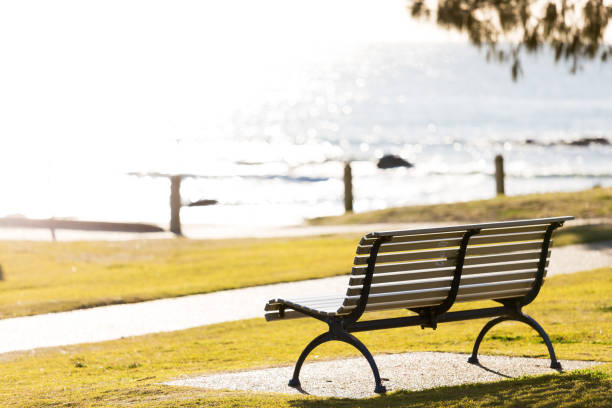 Empty Park Beach Seat By Sea And Bright, Vibrant Morning Sun With No People stock photo