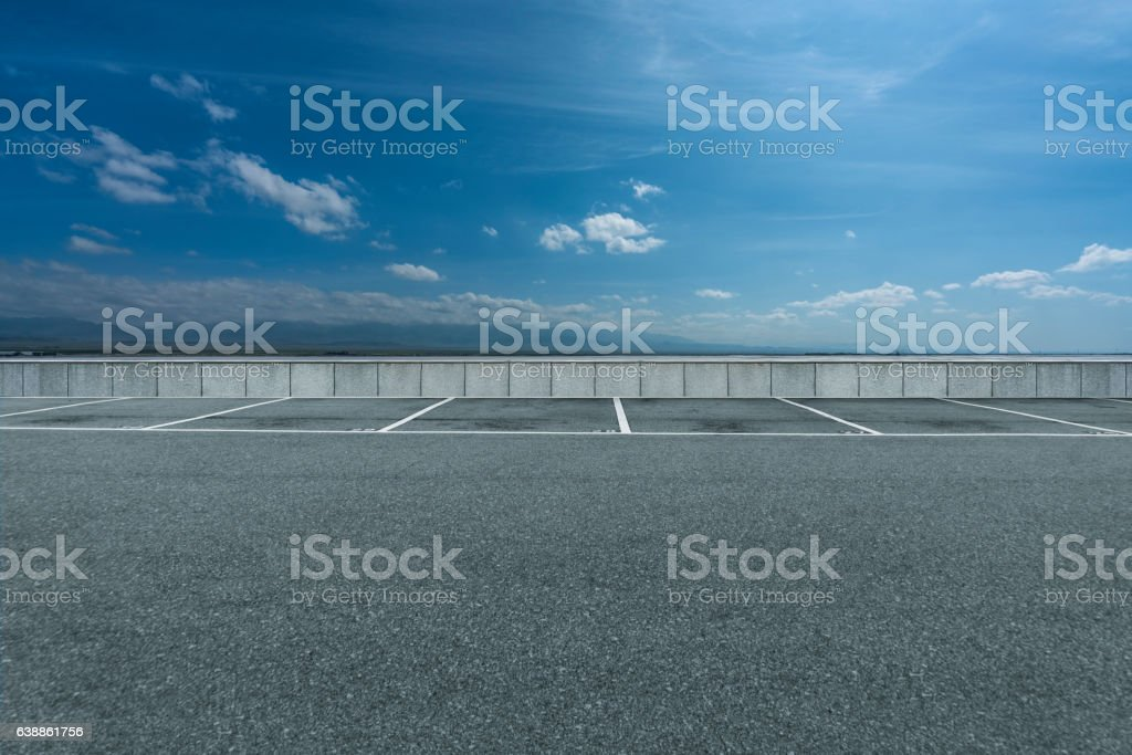 Empty parking lot against blue sky stock photo
