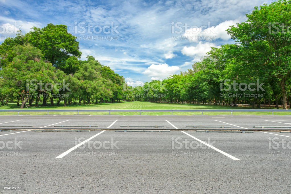 Empty parking lot against green lawn in city park stock photo