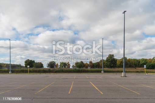Empty parking lot with a forest in the background and partly cloudy sky