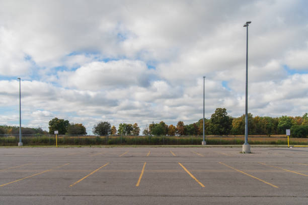 Empty parking lot with a forest in the background and partly cloudy sky Empty parking lot with a forest in the background and partly cloudy sky parking lot stock pictures, royalty-free photos & images