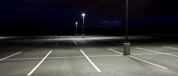 Empty parking lot with white lines An empty parking lot sloping downhill at dusk lit with bright lights. 2.35:1 aspect ratio. parking lot stock pictures, royalty-free photos & images
