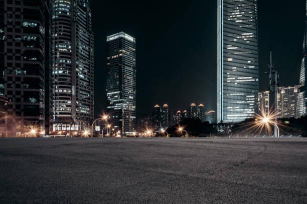lege bestrating en moderne gebouwen in de stad in de nacht - stadsweg stockfoto's en -beelden