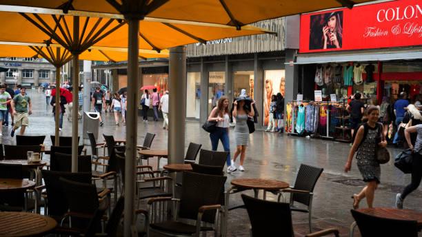 leere straßencafé mit gelben sonnenschirmen an regnerischen innenstadt köln - cafe köln stock-fotos und bilder