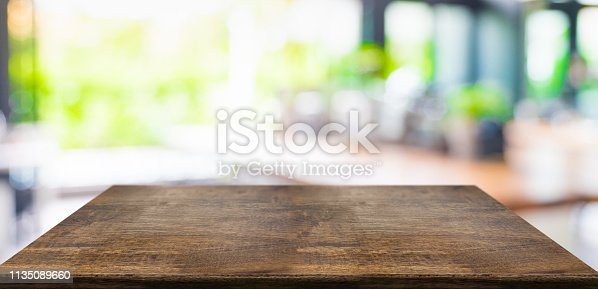 istock Empty perspective hard wood table and blurred garden cafe light background. product display template.Business presentation. 1135089660