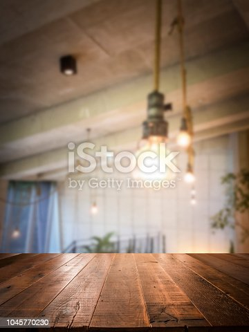 istock Empty perspective wood plank table top with blur coffee shop or restaurant interior background 1045770230