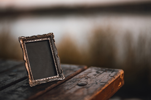 Empty photo frame on a wooden table