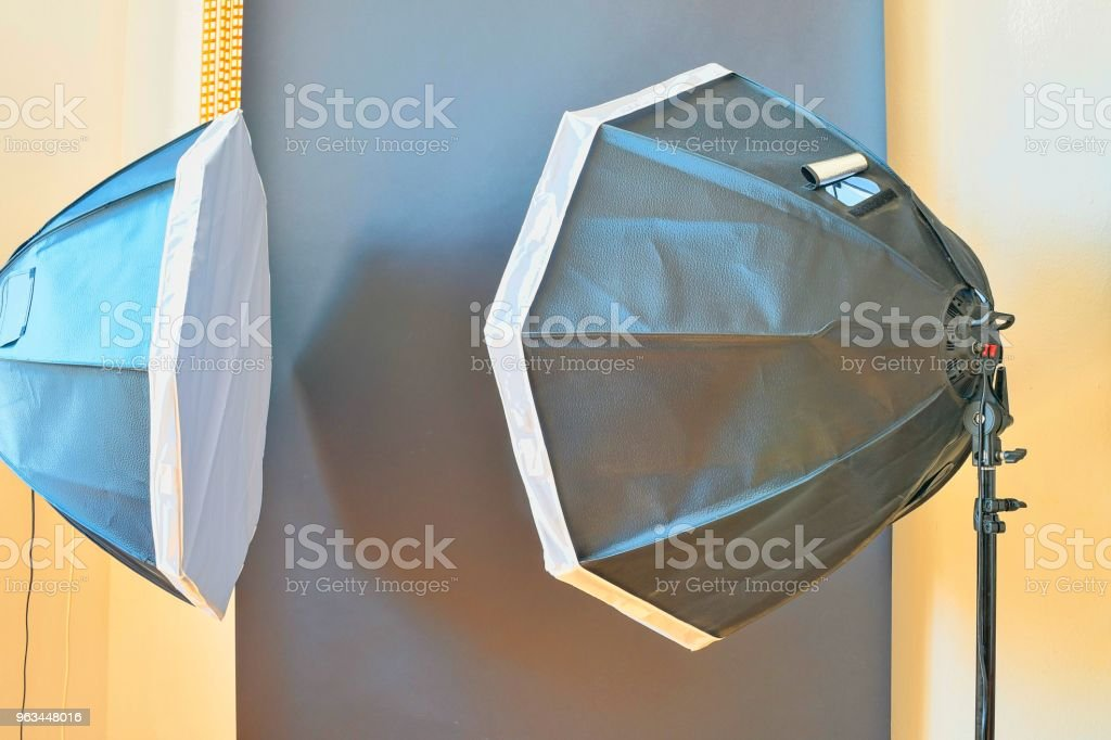 Empty photo studio with lighting equipment. Black background in photo studio - Zbiór zdjęć royalty-free (Aparat fotograficzny)