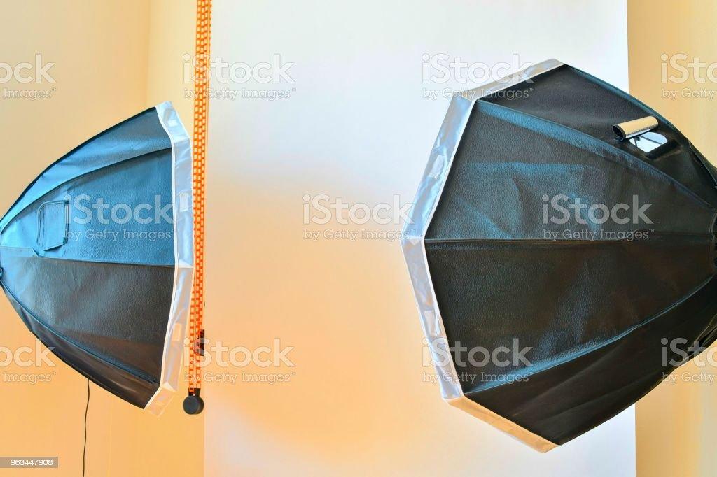 Empty photo studio with lighting equipment. White background in photo studio - Zbiór zdjęć royalty-free (Aparat fotograficzny)