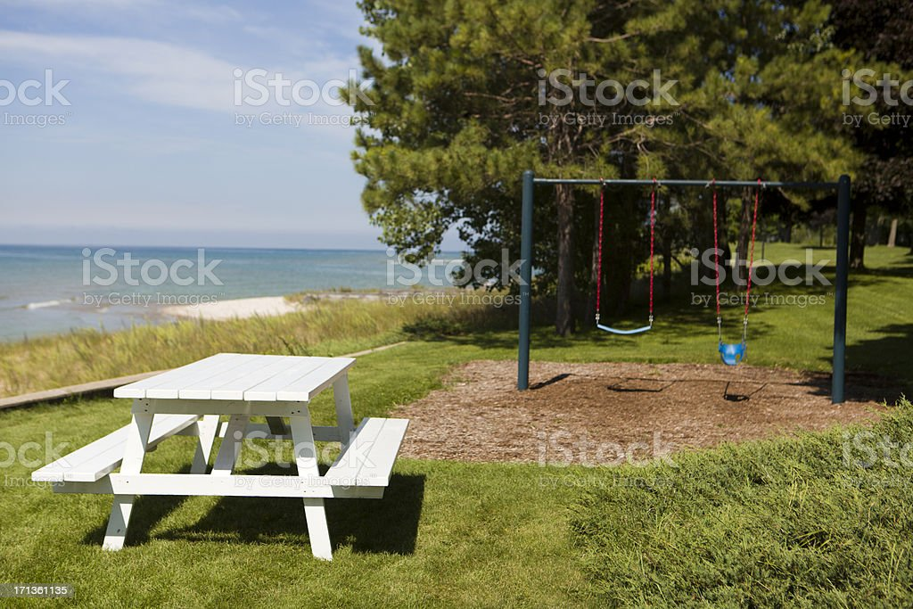 Picnic table in an empty park by swing set and a lake.