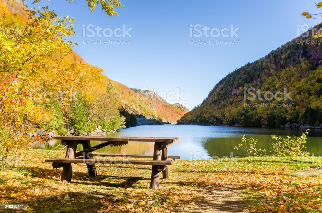 Empty Picnic Table on a Mountain Lake on a Sunny Autumn Day stock photo