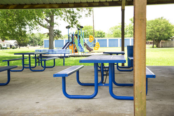 Empty picnic tables under pavilion in small town USA Empty picnic table under pavilion in small town Texas, USA. Blue metal tables.  The virus has kept families out of parks.  Many parks are closed to the public. covid stock pictures, royalty-free photos & images