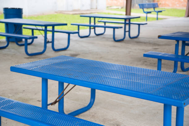 Empty picnic tables under pavilion in small town USA Empty picnic table under pavilion in small town Texas, USA. Blue metal tables.  The virus has kept families out of parks.  Many parks are closed to the public. covid-19 stock pictures, royalty-free photos & images