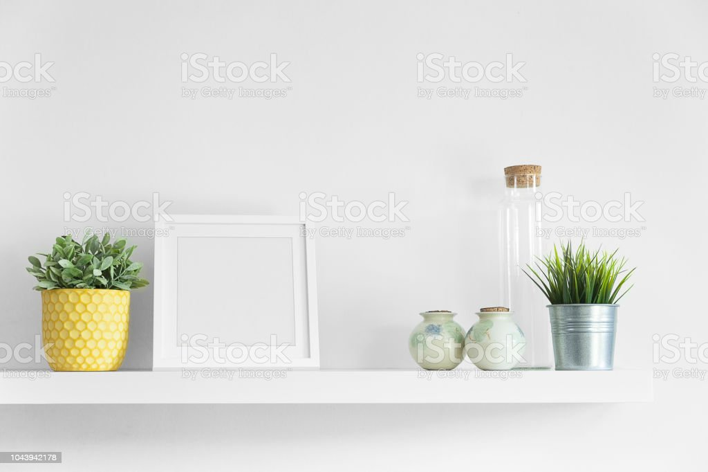 An empty picture frame on a floating shelf surrounded by various...