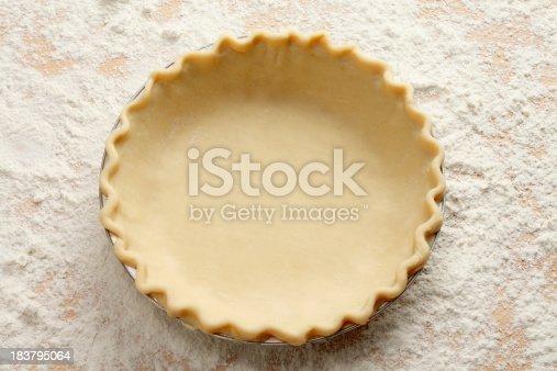 An empty pie crust on a table laden with flour.